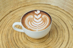 Cappuccino art hot coffee in cup on wood plate Stock Photos