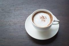 Cappuccino auf einem Holztisch lizenzfreie stockbilder