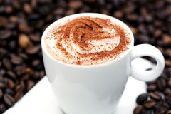 Cappuccino auf Kaffeebohnen Stockbild