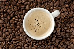 Cappuccino auf Kaffeebohnen Stockfoto