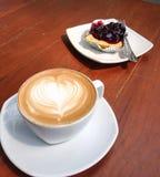Cappuccino avec le coeur en pâtisserie de mousse et de myrtille Images stock