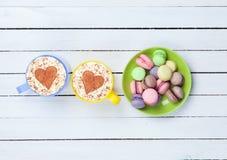 Cappuccino avec le symbole et le macaron de forme de coeur Images libres de droits