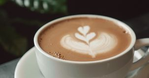 Cappuccino avec un modèle de rosetta d'art de latte dans le crema banque de vidéos