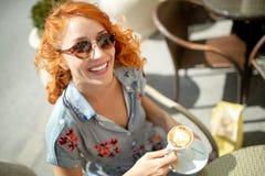 Cappuccino bebendo da mulher bonita nova, caf? no caf? fora fotos de stock royalty free