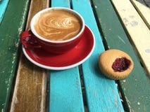 Cappuccino bien créé et gâteau attendant au soleil de matin Images stock
