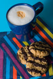 Cappuccino and biscuits. A blue cup of cappuccino with three chocolate biscuits and paper napkin Royalty Free Stock Images
