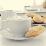 Cappuccino and biscuits on the kitchen table Royalty Free Stock Images