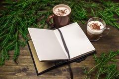 Cappuccino, blocco note, rami attillati nella sera su un fondo di legno Fotografia Stock