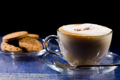 Cappuccino on blue glass table Stock Image