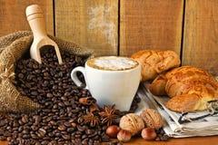Cappuccino, brioches och tidning med bakgrund Fotografering för Bildbyråer