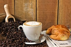 Cappuccino, brioches och tidning med bakgrund Royaltyfri Foto