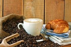 Cappuccino, brioches och tidning med bakgrund Royaltyfri Fotografi