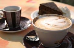 Cappuccino, café express et gâteau italiens Images stock