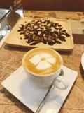 Cappuccino caldo con arte del latte fotografie stock