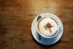 Cappuccino chaud dans la tasse blanche sur la table en bois Photos stock