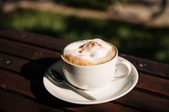 Cappuccino chaud dans la tasse sur la table en bois Photographie stock