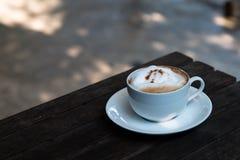 Cappuccino chaud dans la tasse sur la table en bois Image stock