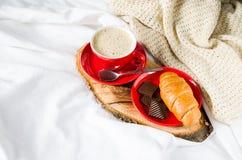 Cappuccino, chocolat et croissant sur un lit Photographie stock