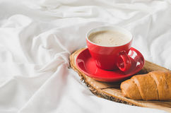 Cappuccino, chocolat et croissant sur un lit Images libres de droits