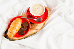 Cappuccino, chocolat et croissant sur un lit Photos libres de droits