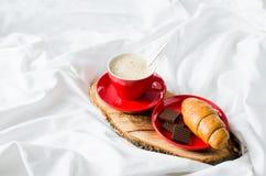 Cappuccino, chocolat et croissant sur un lit Photo stock