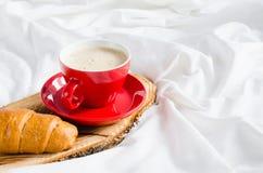 Cappuccino, chocolat et croissant sur un lit Photos stock