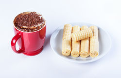 Cappuccino with chocolate chip, wafer rolls, red cup. Stock Photography
