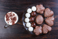 Cappuccino with chocolate chips, coconut candy, chocolate candy Stock Photos