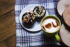 Cappuccino and chocolate cupcakes Stock Photos