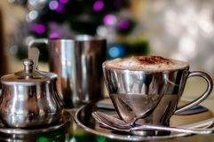 A Cappuccino at Christmas time. A hot cup of Cappuccino in a silver cup with pots of milk and sugar in selective focus on colorful fairy lights bokeh blurred Stock Photo