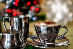Cappuccino with Chritmas fairy lights Bokeh. A hot cup of Cappuccino in a silver cup with pots of milk and sugar in selective focus with Christmas fairy lights Royalty Free Stock Photo
