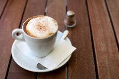Cappuccino with cinnamon. White cup on wooden table Stock Photos