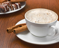 Cappuccino with cinnamon bark and plate of sweets Stock Image