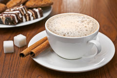 Cappuccino, cinnamon, lump sugar and sweets Royalty Free Stock Photos