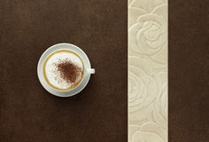 Cappuccino with cocoa on the brown table Royalty Free Stock Image