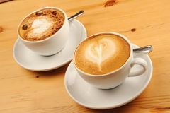 Cappuccino Coffee. Two cups of cappuccino coffee on a wooden restaurant table stock photo