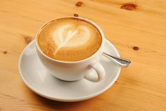 Cappuccino Coffee. Fresh cup of cappuccino coffee on a wooden restaurant table stock images