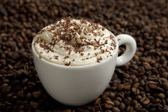 Cappuccino in coffee beans Royalty Free Stock Photos