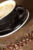 Cappuccino and Coffee Beans. A freshly brewed Cappuccino is in the background with out of focus coffee beans in the foreground Stock Photo