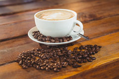 Cappuccino with coffee beans on table royalty free stock photos