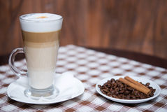 Cappuccino and coffee beans on a tablecloth. Tasty cappuccino and coffee beans on a tablecloth Stock Photos