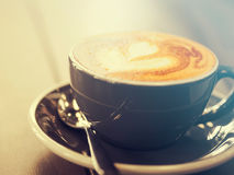 Cappuccino coffee in black cup on wooden table, Soft focus. Summer filter style Royalty Free Stock Images