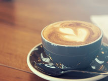 Cappuccino coffee in black cup on wooden table, Soft focus,. Summer filter style Royalty Free Stock Image