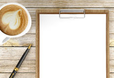 Cappuccino coffee cup with blank papers on clipboard and ballpoint pen, coffee and business background. Cappuccino coffee cup with blank papers on clipboard and stock photography