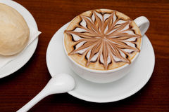Cappuccino, coffee cup and bun Royalty Free Stock Photography