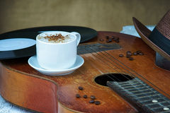Cappuccino coffee cup, guitar, hat and vinyl plate Stock Photos