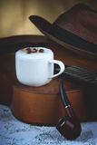 Cappuccino coffee cup, guitar, smoking pipe and hat Royalty Free Stock Photos