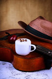 Cappuccino coffee cup, smoking pipe, guitar and hat Stock Photo