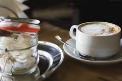 Cappuccino coffee in a cup and sugar refined in a cafe. Close-up royalty free stock image
