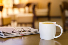 Cappuccino coffee cup on wooden table with newspaper royalty free stock images